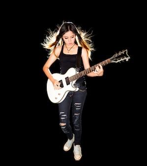 Junge und schöne rockfrau, die die e-gitarre spielt