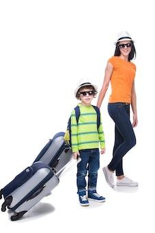 Junge und seine mutter mit koffern vor der reise.