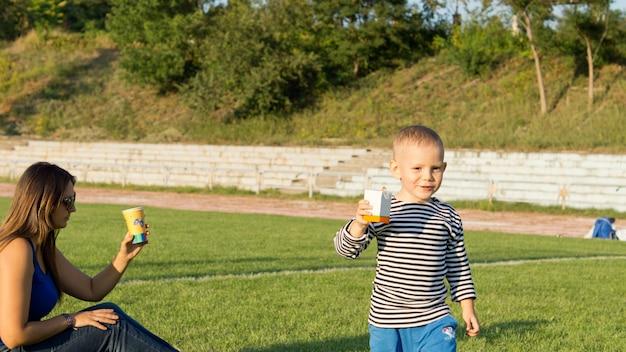 Junge und seine mutter trinken erfrischungen, die auf dem grünen gras eines fußballfeldes im abendsonnenlicht sitzen