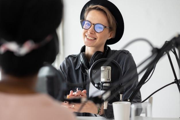 Junge und selbstbewusste europäische frau, die einen podcast in einem tonstudio aufnimmt