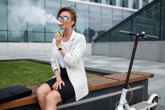 Junge und stilvolle geschäftsfrau, die nach ihrer arbeit vape raucht