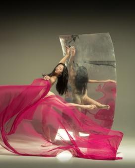 Junge und stilvolle moderne balletttänzerin auf braun mit spiegel