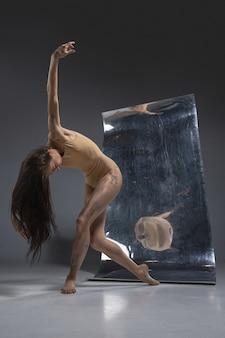 Junge und stilvolle moderne balletttänzerin auf grauer wand mit spiegel- und illusionsreflexionen auf der oberfläche. magie der flexibilität und bewegung. konzept der kreativen kunst tanzen, action und inspiration.