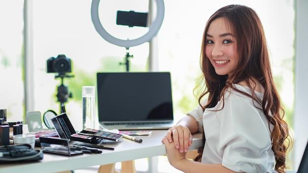 Junge und süße asiatische vloggerin, influencerin oder online-verkäuferin, die mit kosmetikprodukten und dslr-kamera und smartphone und laptop-notebook-computer sitzt und bereit ist, video-live-streams zu übertragen.