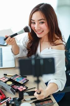 Junge und süße asiatische vloggerin, influencerin oder online-verkäuferin, die smartphone auf langem stock hält, um sich selbst ein video-selfie zu machen und einen live-stream zur kosmetischen überprüfung zu übertragen. online-marketing-konzept.