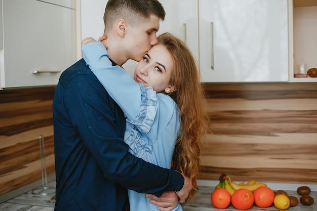 Junge und süße reizende paare, die in der küche mit früchten stehen