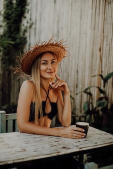 Junge und verführerische frau lächelt und posiert am tisch auf den straßen. hübsche weibliche reisende in ihren ferien in thailand.
