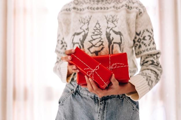 Junge unerkennbare frau hält in einer geschenkbox in rotem papier.