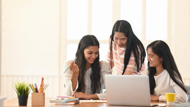 Junge universitätsstudenten, die online mit videokonferenz unterrichten / studieren, während sie vor computer-laptop am hölzernen schreibtisch über bequemem schlafzimmer sitzen