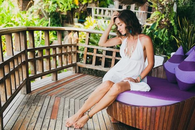 Junge unschuldige reine schöne frau träumt, sitzt auf der couch im weißen kleid, romantisch, lyrisch, denkend, grüne tropische natur, sommer, entspannt, kühlend, beine, resorthotel