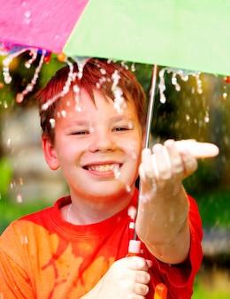 Junge unter einem regenschirm während eines regens.