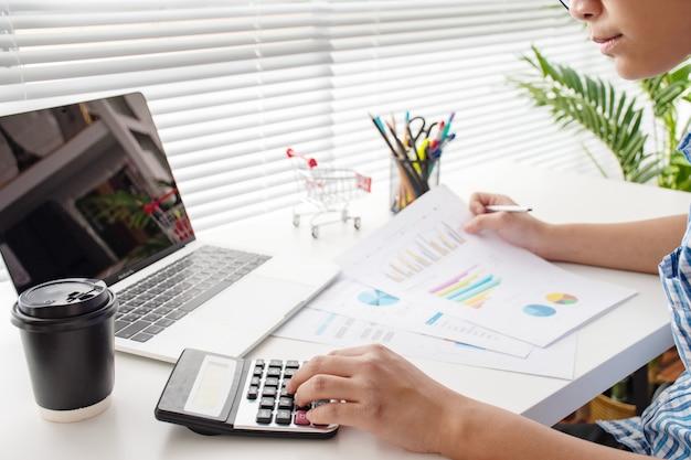 Junge unternehmen berechnen finanzdiagramme auf dem schreibtisch ernsthaft