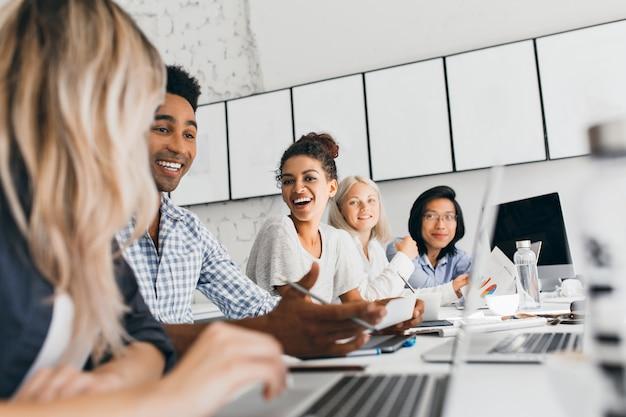 Junge unternehmer diskutieren etwas mit einem lächeln während der konferenz. innenporträt von internationalen mitarbeitern, die mit laptops im büro sitzen und über arbeit sprechen.