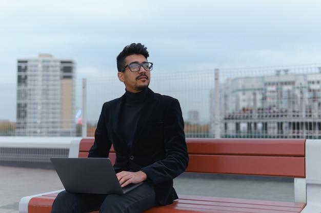 Junge unternehmer in brillen arbeiten am laptop im freien sitzen.