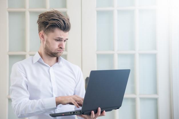 Junge unternehmer suchen laptop notebook mit geschockten negativen stress haltung