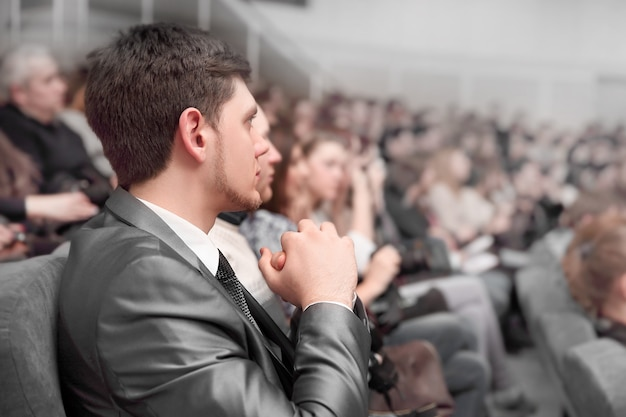 Junge unternehmer und pressevertreter sitzen im konferenzsaal. geschäftstreffen