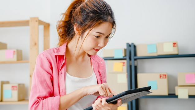 Junge unternehmerin aus asien prüft die produktbestellung auf lager und speichert sie auf dem tablet-computer zu hause. kleinunternehmer, online-marktzustellung, freiberufliches lifestyle-konzept.