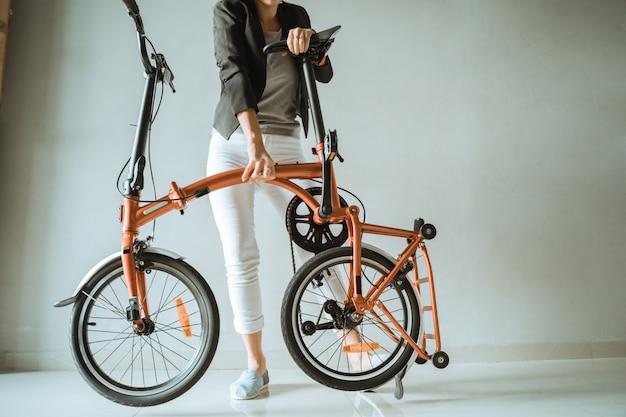 Junge unternehmerin bereitet ein faltrad von zu hause aus vor