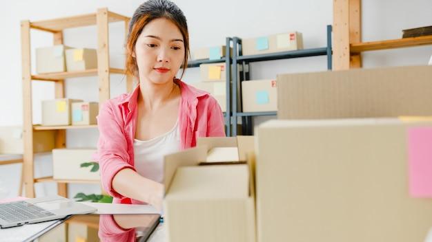 Junge unternehmerin des asiatischen unternehmers überprüfen produktbestellung auf lager und speichern auf computer-laptop-arbeit zu hause büro. kleinunternehmer, online-marktzustellung, freiberufliches lifestyle-konzept.