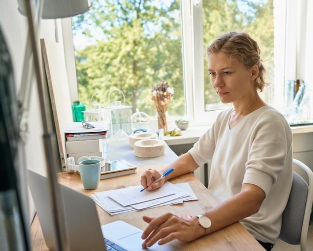 Junge unternehmerin designer, die auf papierblatt schreibt, laptop betrachtet, ernstes fraudenken