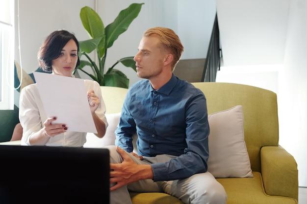 Junge unternehmerin, die auf das diagramm im bericht zeigt, wenn sie ihre gedanken und schlussfolgerungen mit der kollegin beim treffen teilt