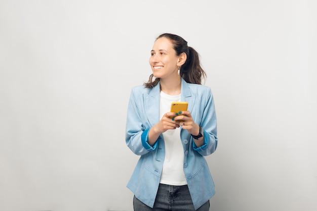 Junge unternehmerin hält ihr telefon und schaut beiseite.