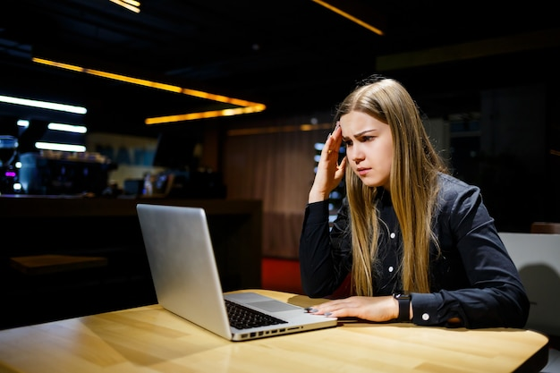 Junge unternehmerin sitzt am computer und hat kopfschmerzen von einem langen arbeitstag