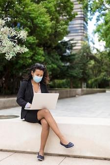 Junge unternehmungslustige hispanische frau, die draußen mit einem laptop arbeitet. sie trägt eine medizinische maske.