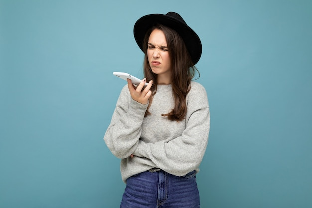 Junge unzufriedene brünette frau mit schwarzem hut und grauem pullover, die smartphone hält und zur seite schaut, isoliert auf hintergrundgesprächen.