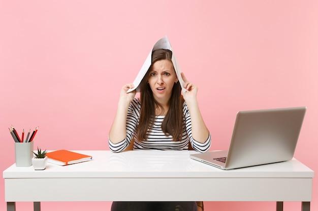 Junge unzufriedene frau, die papierdokumente in der nähe des kopfes hält und an einem projekt arbeitet, während sie mit laptop im büro sitzt