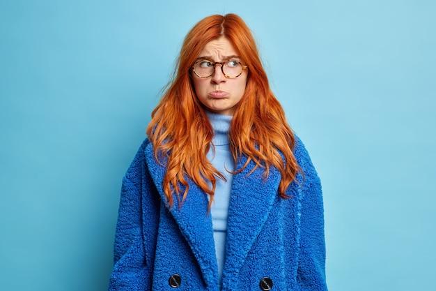 Junge unzufriedene frau spitzt lippen und schaut mit mürrischem ausdruck beiseite, gekleidet in rollkragenpullover und blauem wintermantel.