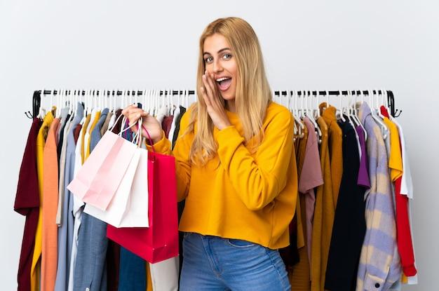 Junge uruguayische blonde frau in einem bekleidungsgeschäft und hält einkaufstaschen, die etwas flüstern