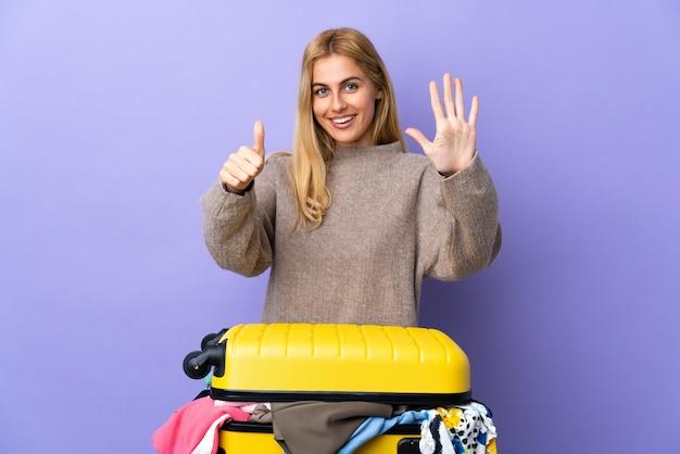 Junge uruguayische blonde frau mit einem koffer voller kleider über isolierter lila wand, die sechs mit den fingern zählt