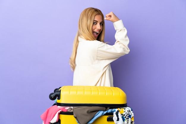 Junge uruguayische blonde frau mit einem koffer voller kleidung über isolierter lila wand, die starke geste tut