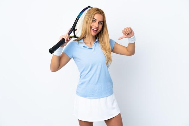 Junge uruguayische blonde frau über isolierter weißer wand, die tennis spielt und stolz auf sich ist