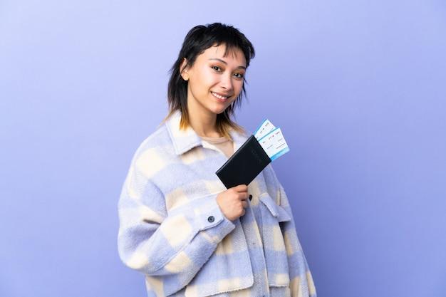 Junge uruguayische frau auf isoliertem purpur glücklich im urlaub mit pass und flugtickets