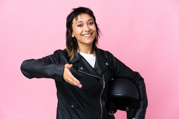 Junge uruguayische frau, die einen motorradhelm über lokalem rosa hintergrundhandschütteln nach gutem geschäft hält