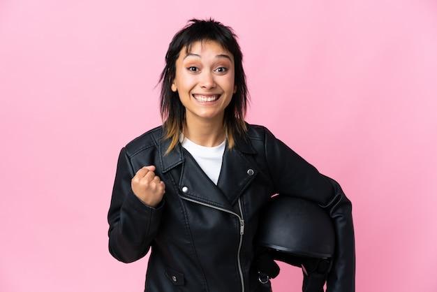 Junge uruguayische frau, die einen motorradhelm über rosa wand hält, die einen sieg feiert