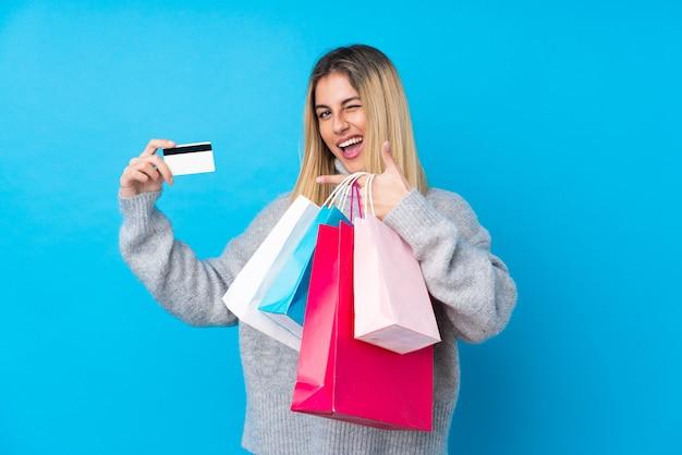 Junge uruguayische frau, die einkaufstaschen und eine kreditkarte hält