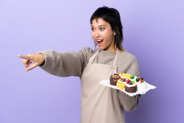 Junge uruguayische frau, die viele verschiedene minikuchen über lila wand hält, die weg zeigt