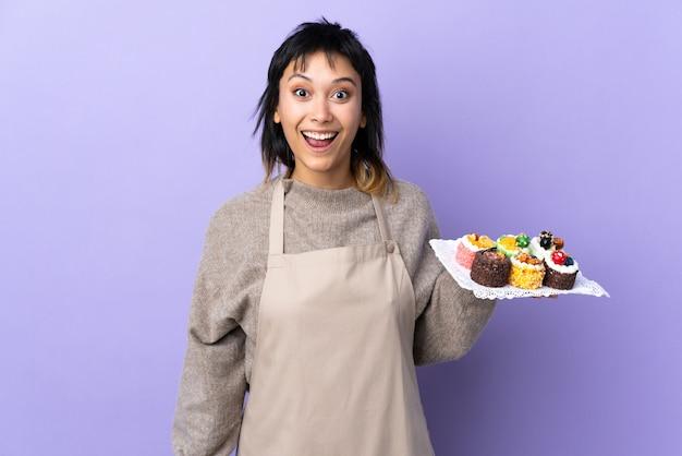 Junge uruguayische frau, die viele verschiedene minikuchen über lila wand mit überraschendem gesichtsausdruck hält
