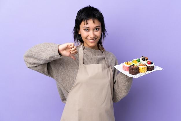 Junge uruguayische frau, die viele verschiedene minikuchen über lila wand stolz und selbstzufrieden hält
