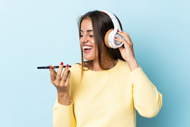 Junge uruguayische frau lokalisiert auf blaue hörende musik mit einem handy und gesang
