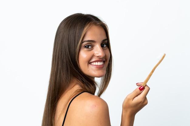 Junge uruguayische frau lokalisiert auf weißer wand mit einer zahnbürste und glücklichem ausdruck