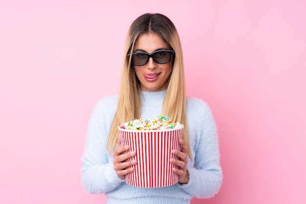 Junge uruguayische frau mit 3d-brille und hält einen großen eimer popcorn