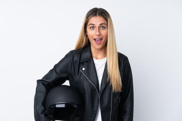 Junge uruguayische frau mit einem motorradhelm mit überraschendem gesichtsausdruck