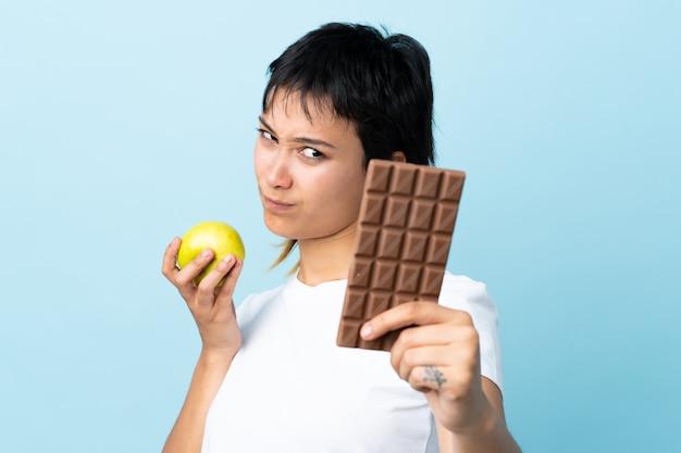 Junge uruguayische frau über der blauen wand, die zweifel hat, während sie eine schokoladentafel in einer hand und einen apfel in der anderen nimmt