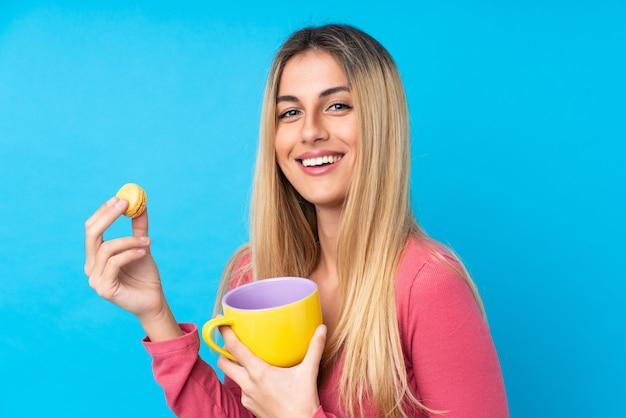 Junge uruguayische frau über der lokalisierten blauen wand, die bunte französische macarons und eine schale milch hält