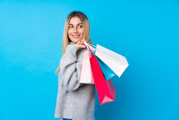 Junge uruguayische frau über der lokalisierten blauen wand, die einkaufstaschen und das lächeln hält