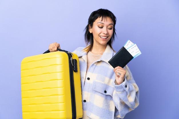 Junge uruguayische frau über isolierte lila wand im urlaub mit koffer und pass